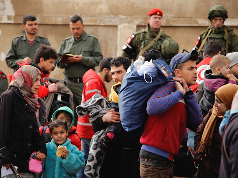 Syrian army and Russian soldiers monitor as rebel fighters and their families evacuate a district of Homs last week: Reuters