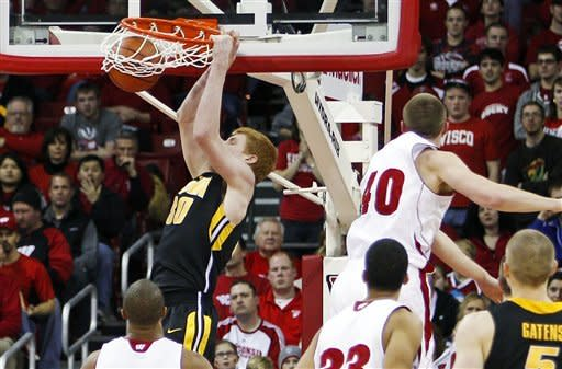Iowa's Aaron White (30) dunks over Wisconsin's Jordan Taylor, left, Rob Wilson (33) and Jared Bergrren (40) during the second half of a college basketball game, Saturday, Dec. 31, 2011, in Madison, Wis. White scored 16 of his 18 points in the second half as Iowa won 72-65. (AP Photo/Andy Manis)