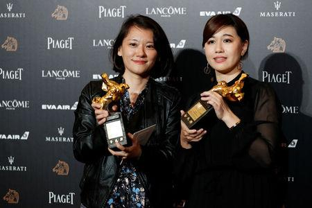 "Taiwan's director Yue Fu (R) poses backstage after winning Best Documentary for her movie ""Our Youth in Taiwan"" at the 55th Golden Horse Awards in Taipei"