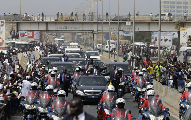 French President Francois Hollande, center left, and Senegalese counterpart Macky Sall wave to supporters lining the streets as they drive from the airport to the Presidential Palace in Dakar, Senegal, Friday, Oct. 12, 2012. Hollande was on a one-day visit to Senegal Friday, en route to Kinshasa, Congo for the Francophone Summit. (AP Photo/Rebecca Blackwell)
