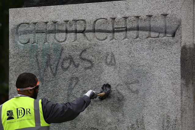A man cleans graffiti from the statue on Monday. (PA)
