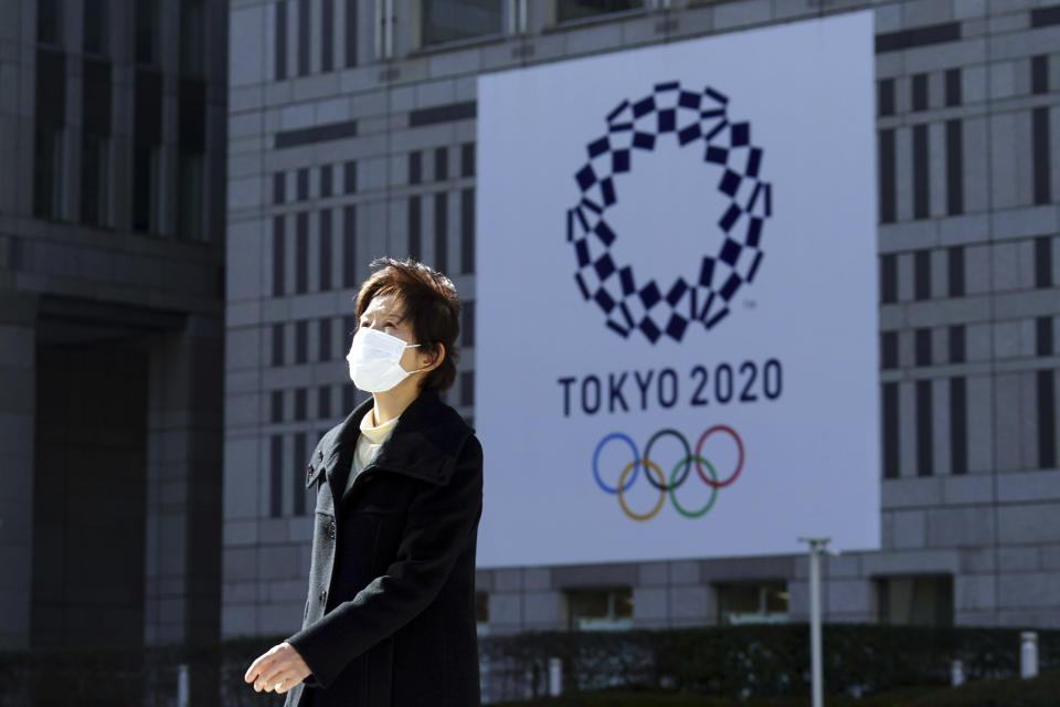 A woman wearing a protective mask to help curb the spread of the coronavirus walks near a banner of the Tokyo 2020 Olympics in Tokyo Tuesday, Jan. 19, 2021. The Tokyo Olympics are to open in six months on July 23. Interestingly, Tokyo organizers have no public program planned to mark the milestone. There is too much uncertainty for that right now. (AP Photo/Eugene Hoshiko)