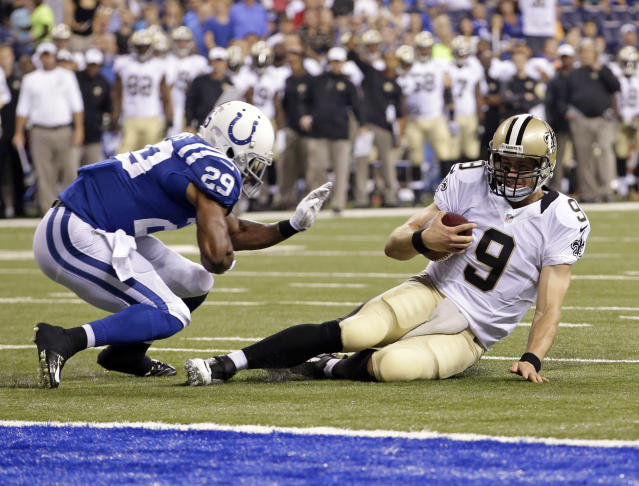New Orleans Saints quarterback Drew Brees slides in under Indianapolis Colts defensive back Marcus Burley during the first half of an NFL preseason football game in Indianapolis, Saturday, Aug. 23, 2014. (AP Photo/AJ Mast)