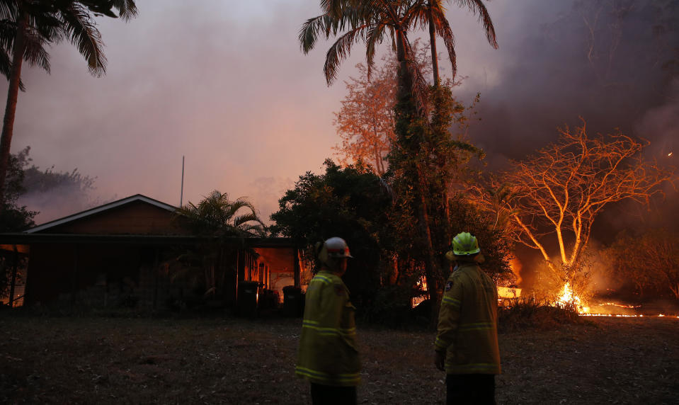 A bushfire in Hillville moves in on a house near the Pacific Highway, north of Nabiac in the Mid North Coast region of NSW, on Tuesday. Source: AAP
