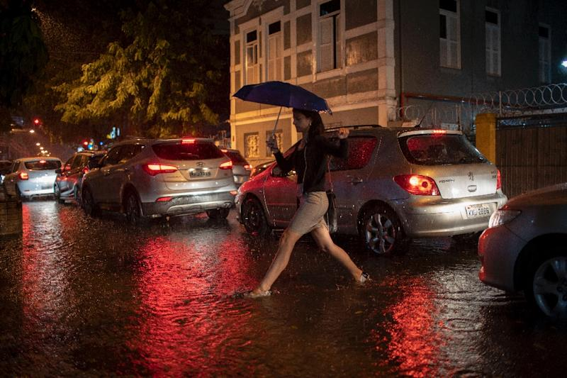 A woman crosses a street in Botafogo neighborhood in Rio de Janeiro, Brazil, as a downpour floods several areas of the city on April 8, 2019. (AFP Photo/Mauro PIMENTEL)
