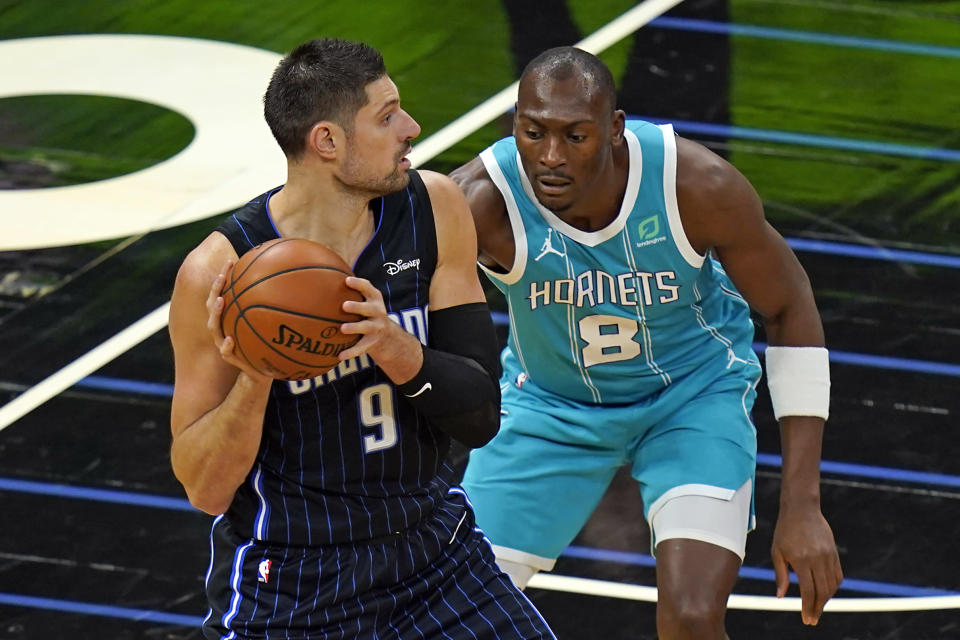 Orlando Magic center Nikola Vucevic (9) looks to pass the ball as Charlotte Hornets center Bismack Biyombo (8) defends during the first half of an NBA basketball game, Monday, Jan. 25, 2021, in Orlando, Fla. (AP Photo/John Raoux)