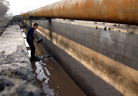 A worker shovels cast-off tailings out of a channel underneath a pipeline that transports crushed mineral ore containing rare earths to a disposal dam near Xinguang Village, located on the outskirts of the city of Baotou in China's Inner Mongolia Autonomou