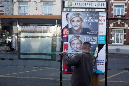 A member of the National Front party pastes a poster on a free billboard for French far right National Front political party leader Marine Le Pen for the upcoming presidential elections, in Henin-Beaumont