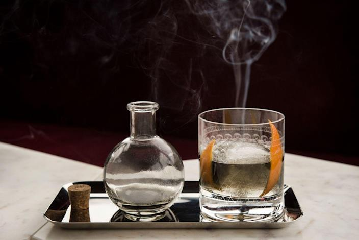 """<p><strong>Ingredients</strong></p><p>1 oz Makers Mark bourbon<br>1 oz Del Maguey mezcal infused with smoked Jamaican peppers*<br>Dash of Jerry Thomas aromatic bitters <br>1/8 tsp activated charcoal<br>Cedar smoke<br>Sugar Cube <br>Garnish with lemon or orange peel </p><p><strong>Ingredients</strong></p><p>Combine the sugar cube, bourbon, smoked mezcal and activated charcoal in a rocks glass. Add a dash of the aromatic bitters and stir. Mix together and set aside. Take a stick of cedar wood and torch it - then blow it out. Place the stick into the glass without the cocktail and then cover it with a coaster. Let the glass smoke up and then remove the cedar. Pour the final cocktail into the glass and garnish with a lemon or orange peel.</p><p><strong>*Mezcal with Jamaican peppers: </strong>For a 750 ml bottle of tequila, lightly char 1 Jamaican pepper without the seeds on a flame or grill and then mix it into the tequila. Steep the pepper for roughly 15 minutes (taste along the way for spiciness).</p><p><em>By Mixologist Amir Babayoff for <a href=""""http://www.opheliany.com/"""" rel=""""nofollow noopener"""" target=""""_blank"""" data-ylk=""""slk:Ophelia"""" class=""""link rapid-noclick-resp"""">Ophelia</a></em></p>"""
