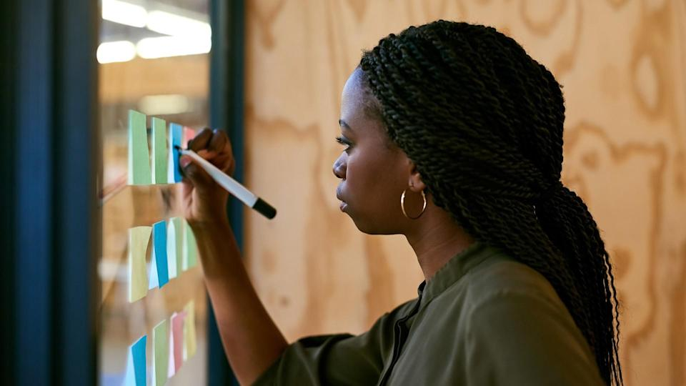 Cropped shot of a young designer writing her ideas on adhesive notes.