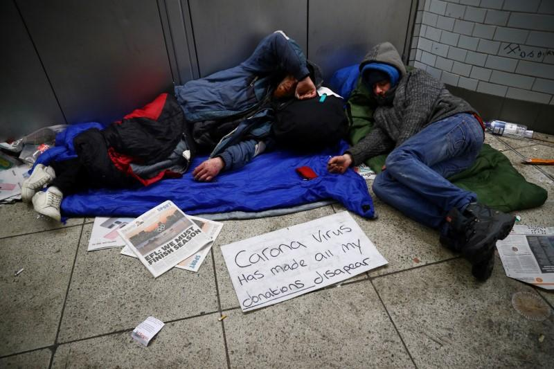FILE PHOTO: Homeless people inside Westminster underground station display a sign