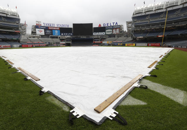 A tarp covers the field at Yankee Stadium after a baseball game between the New York Yankees and the Baltimore Orioles was postponed due to a forecast for inclement weather, Tuesday, May 14, 2019, in New York. (AP Photo/Kathy Willens)