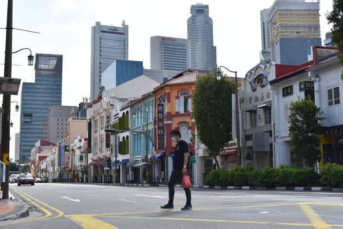 A man wearing a face mask crosses the street in Singapore's Chinatown district on Tuesday, May 12, 2020. Singapore has allowed selected businesses such as traditional Chinese medicine medical halls, home-based establishments, food manufacturing, selected food retail outlets, laundry services, traditional barbers and pet supplies to reopen May 12 in a cautious rollback of a two-month partial lockdown to curb the spread of COVID-19 infections in the city-state. (AP Photo/YK Chan)