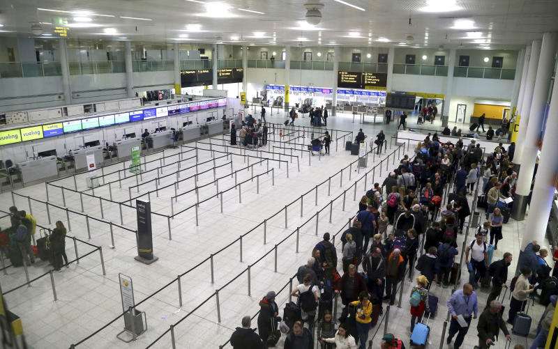 Passengers queue for flights at Gatwick Airport as the airport and airlines work to clear the backlog of flights delayed by a drone incident earlier in the week, in Crawley, England, Saturday, Dec. 22, 2018. London's Gatwick Airport took strides toward running a full schedule Saturday as police questioned a man and a woman in connection with the drone intrusions that caused mayhem for tens of thousands of holiday travelers. (Gareth Fuller/PA via AP)