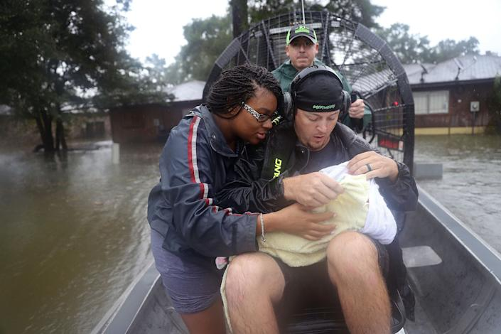 Shardea Harrison looks at her 3-week-old baby, Sarai Harrison, being held by Dean Mize as he and Jason Legnon used his airboat to rescue them after their neighborhood was inundated with flooding in Houston.