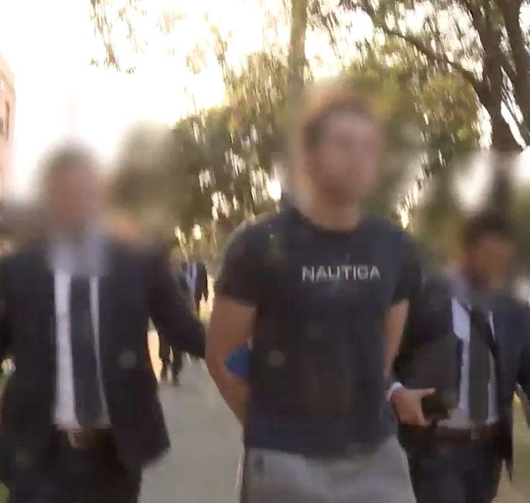 Police walk either side of Youssef Uweinat after he is arrested from his Sydney home.