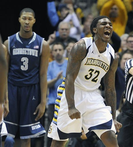 Georgetown 's Mikael Hopkins (3) looks on as Marquette 's Jae Crowder (32) celebrates a basket during the second half of an NCAA college basketball game Saturday, March 3, 2012, in Milwaukee. (AP Photo/Jim Prisching)