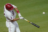 Los Angeles Angels' Mike Trout hits a foul ball which was caught by Texas Rangers right fielder Joey Gallo during the third inning of a baseball game Friday, Sept. 18, 2020, in Anaheim, Calif. (AP Photo/Ashley Landis)
