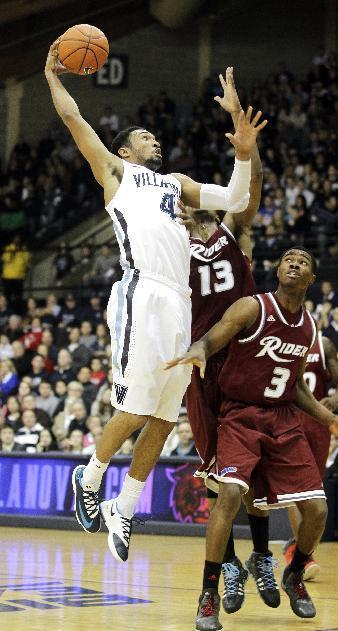 Villanova's Darrun Hilliard (4) drives to the basket past Rider's Daniel Stewart (13) and Jimmie Taylor (3) in the first half of an NCAA college basketball game, Saturday, Dec. 21, 2013, in Villanova, Pa. (AP Photo/Laurence Kesterson)