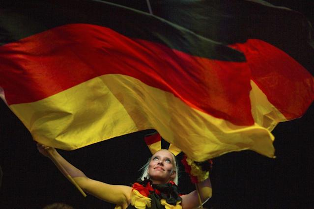 BERLIN, GERMANY - JUNE 09: A German soccer fan cheers with German flags at the end of their team's first game of the Euro 2012 at a public viewing zone called 'fan mile' on June 9, 2012 in Berlin, Germany. Germany won 1:0 versus Portugal. (Photo by Carsten Koall/Getty Images)