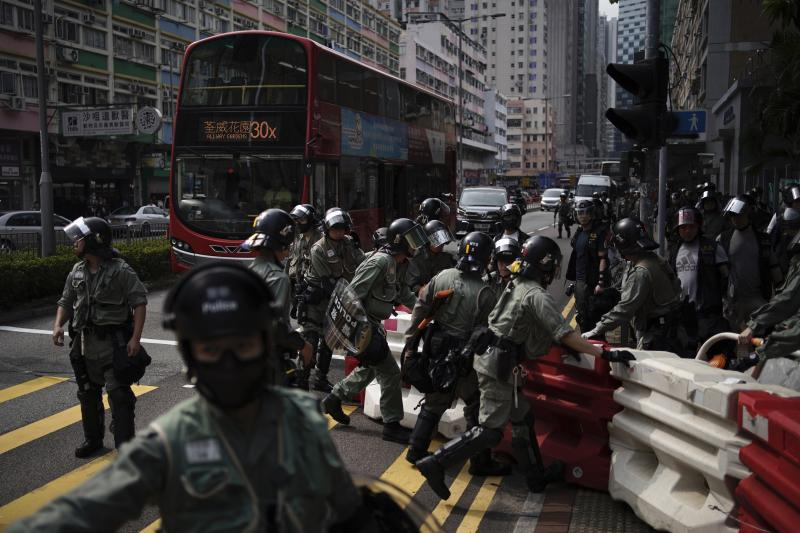 Police remove a road block set up by anti government protesters at Tseun Wan, Hong Kong, Sunday, Oct.13, 2019. The semi-autonomous Chinese city is in its fifth month of a movement that initially began in response to a now-withdrawn extradition bill that would have allowed Hong Kong residents to be tried for crimes in mainland China. The protests have since ballooned to encompass broader demands for electoral reforms and an inquiry into alleged police abuse. (AP Photo/Felipe Dana)