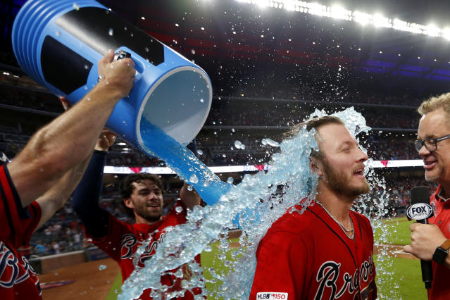 Atlanta Braves' Josh Donaldson, second from right, is doused by Dansby Swanson after driving in the winning run with a base hit in the ninth inning of a baseball game against the Washington Nationals, Friday, July 19, 2019, in Atlanta. (AP Photo/John Bazemore)