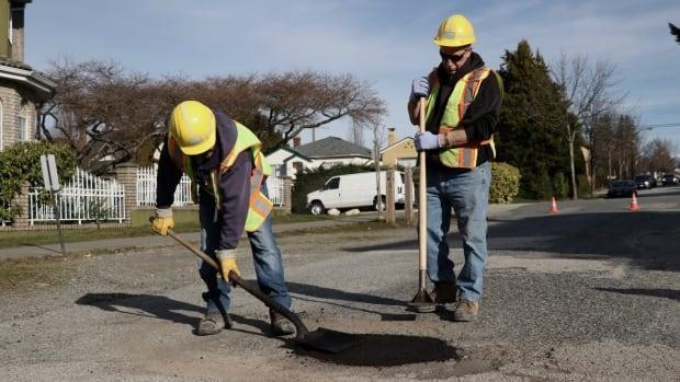 A City of Vancouver crew works on a pothole in 2018. When it comes to fixing road defects, the city's policy is to wait until a complaint is filed. (Rafferty Baker/CBC - image credit)