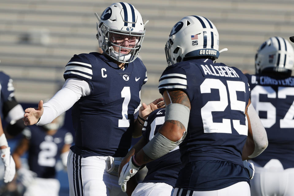 BYU quarterback Zach Wilson (1) congratulates running back Tyler Allgeier (25) after his first quarter touchdown against North Alabama during an NCAA college football game Saturday, Nov. 21, 2020, in Provo, Utah. (AP Photo/Jeff Swinger, Pool)