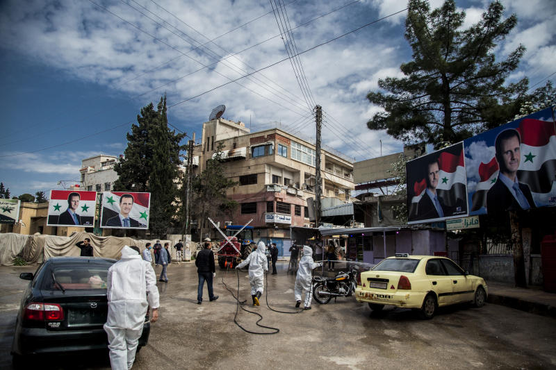 FILE - In this March 24, 2020 file photo, workers spray disinfectant to prevent the spread of the coronavirus, on a street lined with billboards showing Syrian President Bashar Assad, in Qamishli, Syria. In some cells in Iran, Syria and other countries in the Middle East, prisoners are crammed in by the dozens, with little access to hygiene or medical care. So if one infection gets in, the novel coronavirus could run rampant. Among the vulnerable prison populations are tens of thousands of political detainees, jailed for anything from advocating for democracy, holding protests or simply criticizing autocratic leaders. (AP Photo/Baderkhan Ahmad, File)