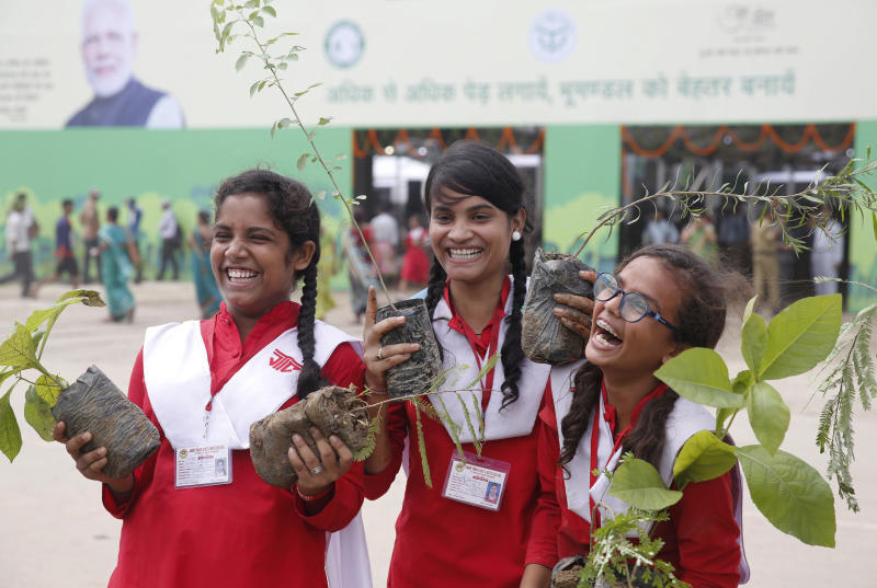 Indian school children hold saplings distributed by the government in Prayagraj, India , Friday, Aug. 9, 2019. More than a million Indians planted saplings as part of a government campaign to tackle climate change and improve environment in the country's most populated state. (AP Photo/Rajesh Kumar Singh)