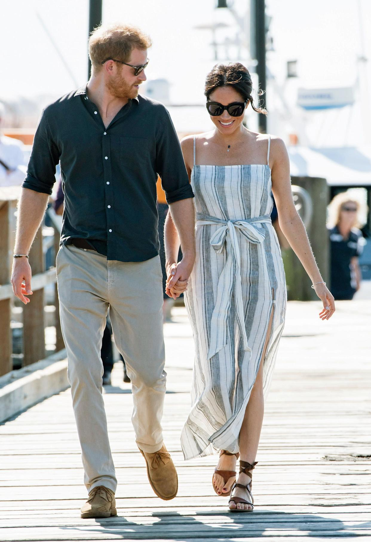 "The duchess wears a striped dress by <a href=""https://www.thereformation.com/products/pineapple-dress"" rel=""nofollow noopener"" target=""_blank"" data-ylk=""slk:Reformation"" class=""link rapid-noclick-resp"">Reformation</a>&nbsp;(which is currently unavailable online) on day 7 of the royal tour. The royal couple are seen walking along the Kingfisher Bay Jetty on Fraser Island on Oct. 22."