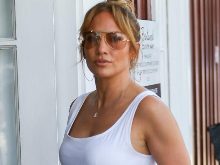 Jennifer Lopez wearing sunglasses, a white top, and white pants in July 2021.