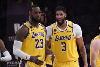 FILE - In this Feb. 21, 2020, file photo, Los Angeles Lakers forward LeBron James, left, stands with forward Anthony Davis during the second half of an NBA basketball game against the Memphis Grizzlies in Los Angeles. James and Davis had the Lakers on course to contend for another NBA title before the coronavirus pandemic upended their first season together. The superstars see no reason they cant continue their quest in Orlando, and Davis even thinks the Lakers chances have improved.(AP Photo/Mark J. Terrill, File)
