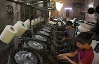 Workshops in Syria's Aleppo used to clatter on into the night before the war, but power cuts mean machines now grind to a halt at 6:00 pm sharp (AFP/-)