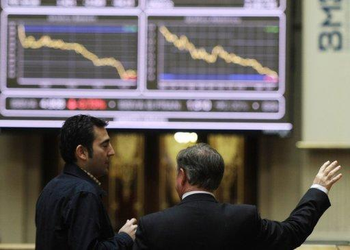 Traders look at the IBEX-35 index curve at Madrid's stock exchange. Spain's borrowing costs shattered euro-era records after Moody's downgraded its debt close to junk-bond status and warned of a growing risk of a full-blown bailout