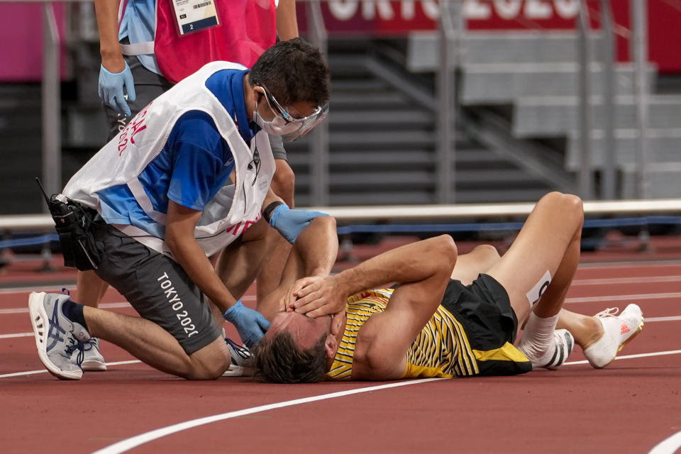 Niklas Kaul, of Germany, is assisted on the track in a heat of the men's decathlon 400-meter at the 2020 Summer Olympics, Wednesday, Aug. 4, 2021, in Tokyo. (AP Photo/Martin Meissner)