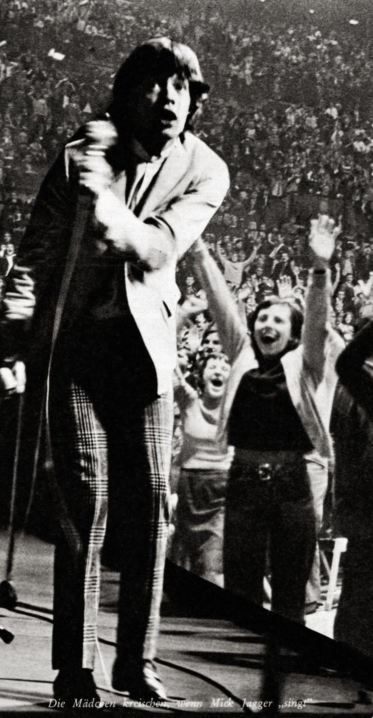 <p>Mick Jagger turns away from extremely enthusiastic fans, while at performing at a concert in Austria, 1965.</p>