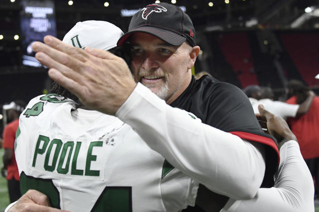 Atlanta Falcons head coach Dan Quinn embraces New York Jets cornerback Brian Poole (34) after the second half an NFL preseason football game, Thursday, Aug. 15, 2019, in Atlanta. (AP Photo/John Amis)