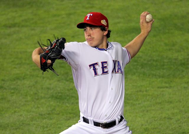 ARLINGTON, TX - OCTOBER 23: Derek Holland #45 of the Texas Rangers pitches in the first inning during Game Four of the MLB World Series against the St. Louis Cardinals at Rangers Ballpark in Arlington on October 23, 2011 in Arlington, Texas. (Photo by Doug Pensinger/Getty Images)