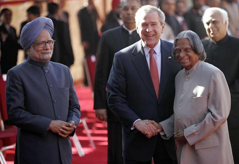 U.S. President George W. Bush shakes hands with Indian President A.P.J. Abdul Kalam while Prime Minister Manmohan Singh looks on during an official welcoming ceremony at the Presidential Palace in New Delhi on March 2, 2006. | Emmanuel Dunand–AFP/Getty Images