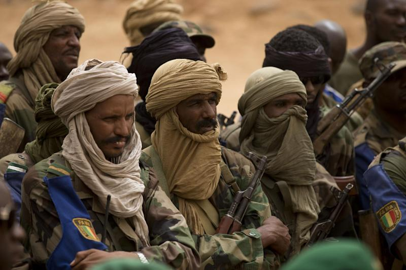 FILE - In this July 27, 2013 file photo, Malian Tuareg soldiers loyal to Col. Major El-Hadj Gamou listen during a visit by Mali's army chief of staff in Kidal, Mali. Malian soldiers and ethnic Tuareg separatist rebels clashed again in the northern desert town of Kidal early Monday, Sept. 30, 2013, a day after trading gunfire downtown in a battle that has raised fears about whether an unraveling peace accord could lead to protracted fighting in the region. (AP Photo/Rebecca Blackwell, File)