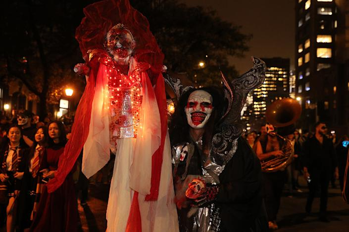 A reveler wears a horror costume carrying a disturbing-looking prop marches in the Village Halloween Parade in New York City. (Photo: Gordon Donovan/Yahoo News)