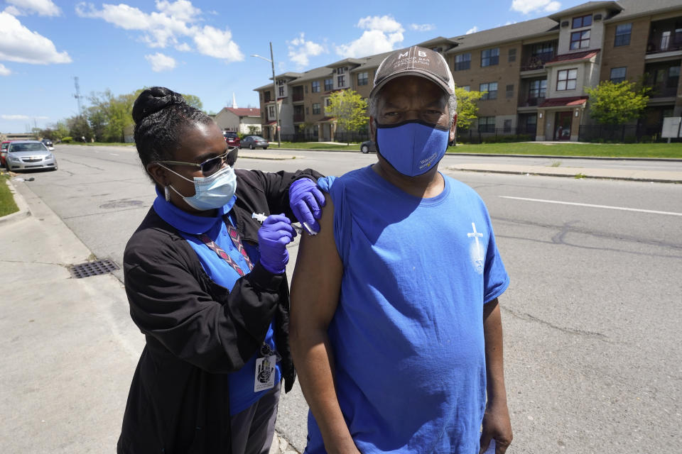 Registered nurse Precious McCormick administers a syringe of Moderna COVID-19 vaccine to Kwame Molette in Detroit, Wednesday, May 12, 2021. In three weeks, more than 40 people have received vaccinations through the program to reach people who normally have little to no access to churches, community centers or other places where vaccines are being given. Mobile care teams consisting of two nurses and a peer support specialist accompany The Salvation Army's Bed & Bread trucks as they cruise Detroit, which lags far behind the state and nearby communities in percentage of people vaccinated. (AP Photo/Paul Sancya)