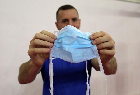 Swedish boxing coach Daniel Nash displays a medical face mask that was provided by a hotel staff ahead of AIBA Women's World Boxing Championships in New Delhi, India, November 12, 2018. REUTERS/Anushree Fadnavis