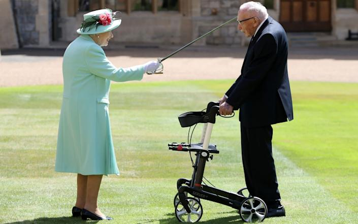 In brilliant summer sunshine the Queen hosted the informal ceremony and spent around five minutes chatting to Sir Tom and his family - PA