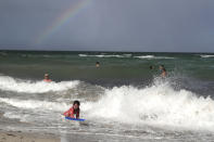 A rainbow is seen on the horizon as people enjoy the waves from a high surf, Friday, July 31, 2020, in Miami Beach, Fla. Forecasters declared a hurricane warning for parts of the Florida coast Friday as Hurricane Isaias drenched the Bahamas on track for the U.S. East Coast. (AP Photo/Lynne Sladky)