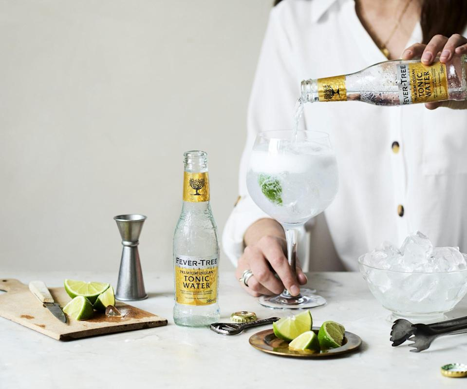 tonic water being poured into glass filled with ice
