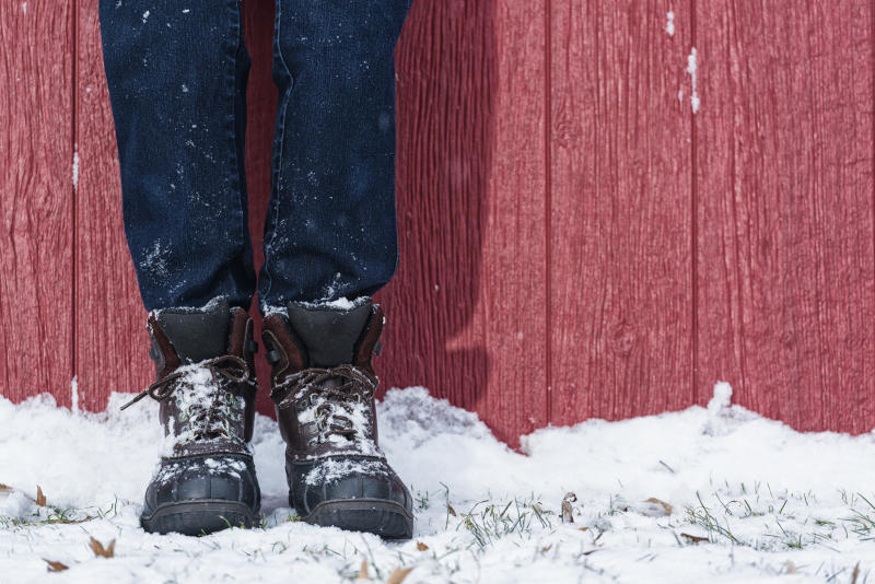 A close-up of a woman's legs wearing duck boots and blue jeans leaning against a red barn in the snow.