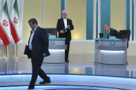 """In this picture made available by Young Journalists Club, YJC, presidential candidates for June 18, elections Abdolnasser Hemmati, left, Saeed Jalili, center, and Alireza Zakani, conclude a part of the final debate of the candidates at a state-run TV studio in Tehran, Iran, Saturday, June 12, 2021. Iran's seven presidential candidates offered starkly different views Saturday in the country's final debate, with hard-liners describing those seeking ties with the West as """"infiltrators"""" and the race's sole moderate warning a hard-line government would only bring more sanctions for the Islamic Republic. (Morteza Fakhri Nezhad/ Young Journalists Club, YJC via AP)"""