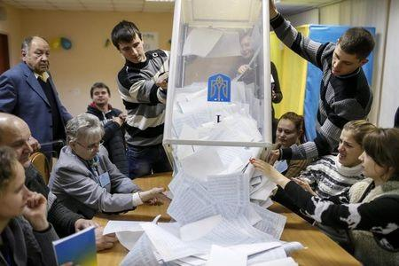 Members of a local electoral commission empty a ballot box at a polling station after voting day in Kiev, October 26, 2014. REUTERS/Gleb Garanich